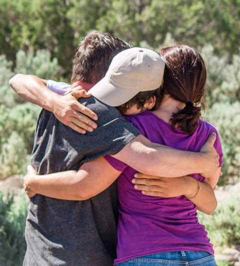 Family hugging at redcliff ascent